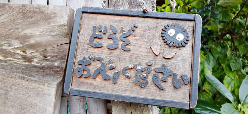龍貓森林裡的小黑炭看板,寫著「どうぞお入りください」(歡迎入內)