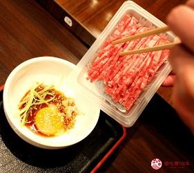 東京高田馬場燒肉激戰區的A5黑毛和牛絕品美味「吟まるJr.」的生拌牛肉「肉膾」(ユッケ)實際將生牛肉放進蛋黃拌醬中