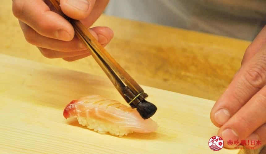 東京高質感壽司店推薦「赤坂 鮨葵」的壽司師傅刷醬油到壽司上中